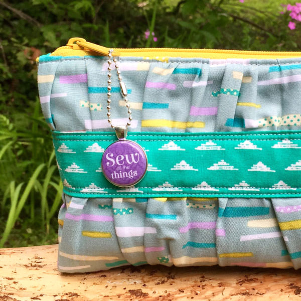 Purple swing tag on a gorgeous Gather Me Up Clutch - Andrie Adornments