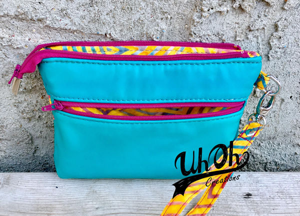 Look at that pop of pink on the zippers of this Gather Me Up Clutch - Andrie Designs