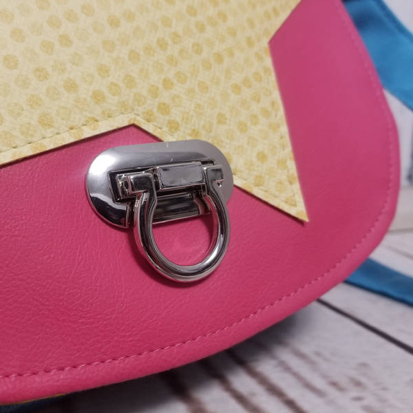 Close up of the turn lock on the bright 'star' motif That Flap Saddlebag - Andrie Designs