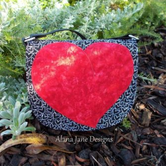 Deep textured red for this 'heart' motif That Flap Saddlebag - Andrie Designs