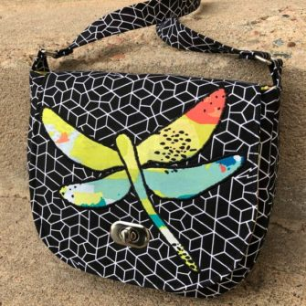 Angled view of the colourful 'dragonfly' motif - That Flap Saddlebag - Andrie Designs