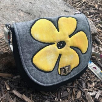 Angled view of the summery 'flower' motif That Flap Saddlebag - Andrie Designs