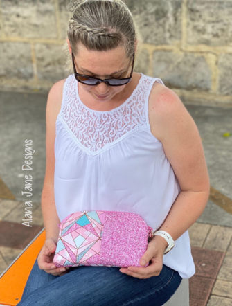 Action shot of the pink and sparkly Gemma Carryall Pouch - Andrie Designs